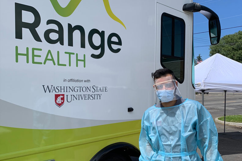 Sorosh Kherghehpoush standing next to the WSU mobile health care unit.