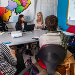 Women talking around a conference table.