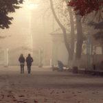People walk along a smoky street.