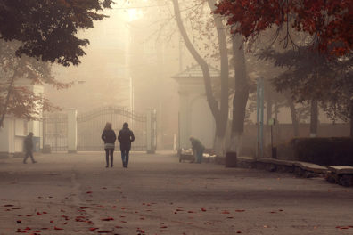 People walk along a smoky street.
