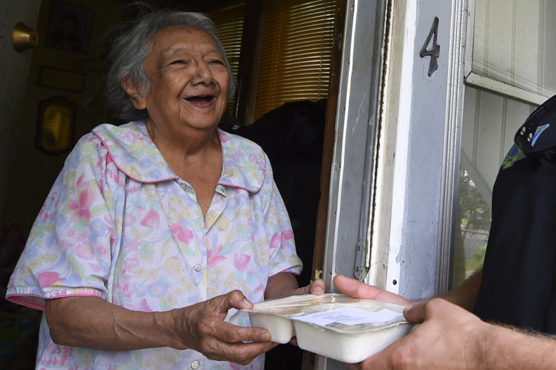 An elderly woman receives a Meals on Wheels delivery.