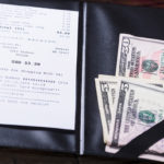 Cash and receipt on a restaurant table.