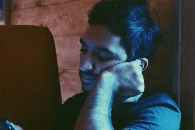 Depressed man looking at his smartphone.