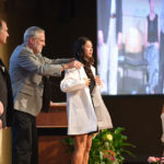 A veterinary medicine graduate receives her white coat