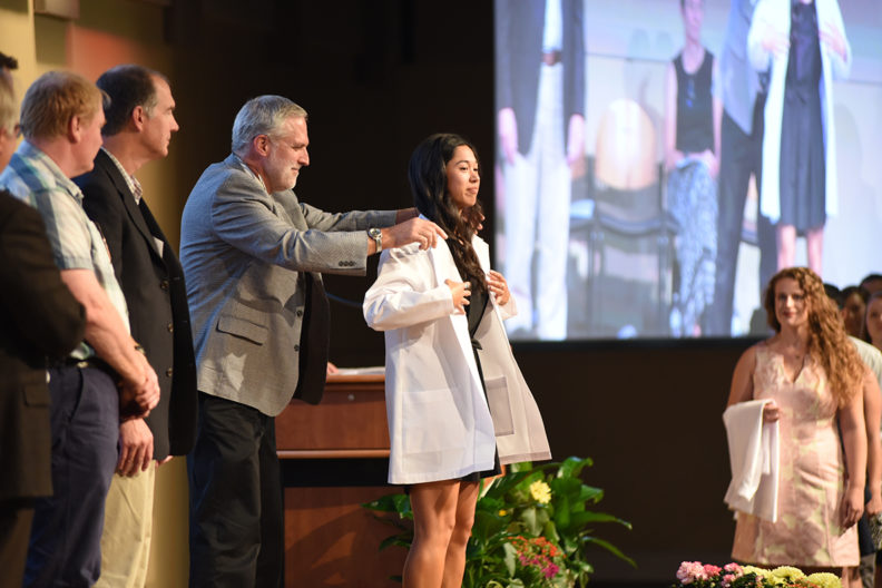 A veterinary medicine graduate receives her white coat