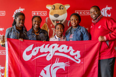 A family of five posing with Butch Cougar mascot and holding a WSU Cougars flag