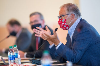 Gov. Jay Inslee wearing a mask and gesturing with his hands during a meeting