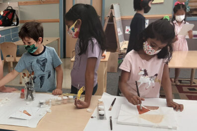 Children painting art projects in a classroom.
