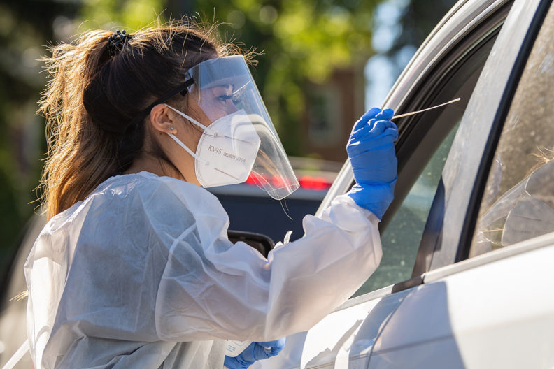 A health care worker reaches through a car window to conduct a COVID-19 test.