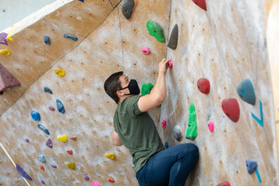 A student climbs on the climbing wall at the UREC center.