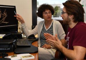 Professor Alla Kostyukova and her graduate student discuss results on a computer screen.