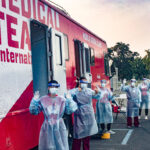Students in PPE stand outside a mobile medical unit.