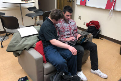 A WSU ROAR student looks at the screen as he and a practicum student work on a laptop.