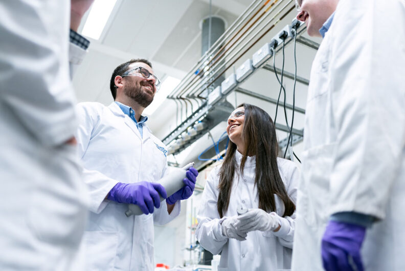 two students in lab coats smiling