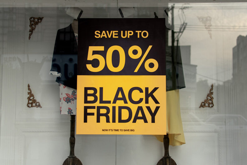 A retail clothing store window with a Black Friday 50% off sale sign