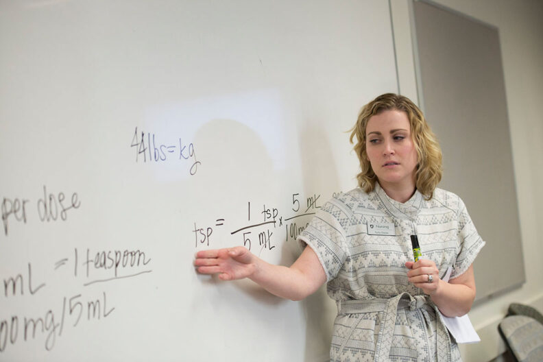 Professor gesturing to equations on a whitebord