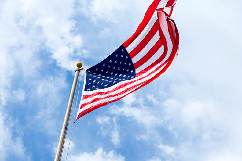 An American flag flying high in the air.