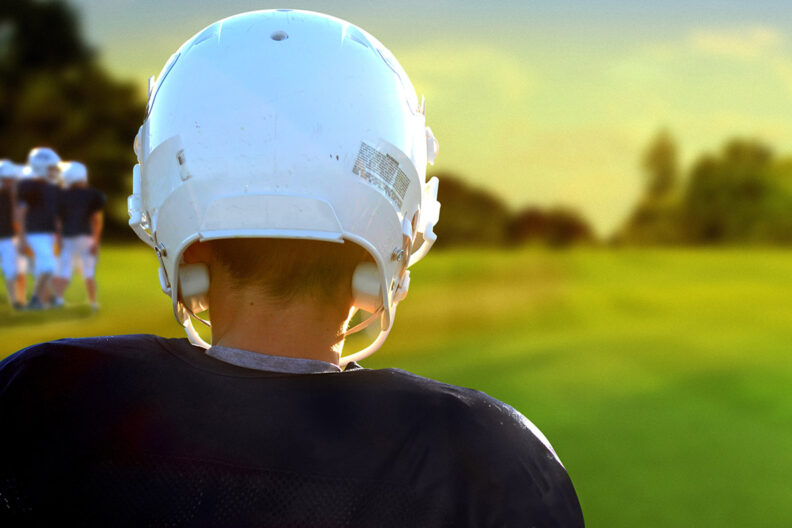 Young football player in a white helmet and blue jersey standing before an empty field.