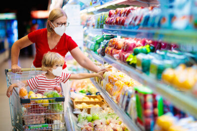 A mother and child wear face masks while grocery shopping.