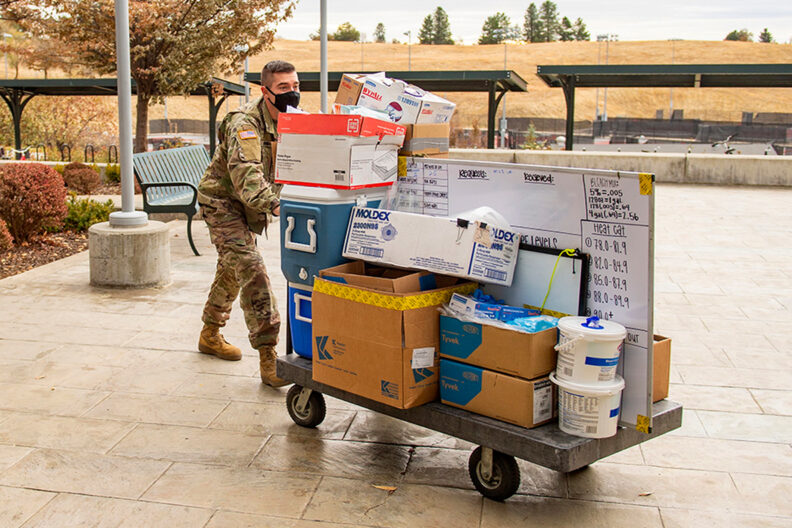 National Guardsman pushing a supply cart.