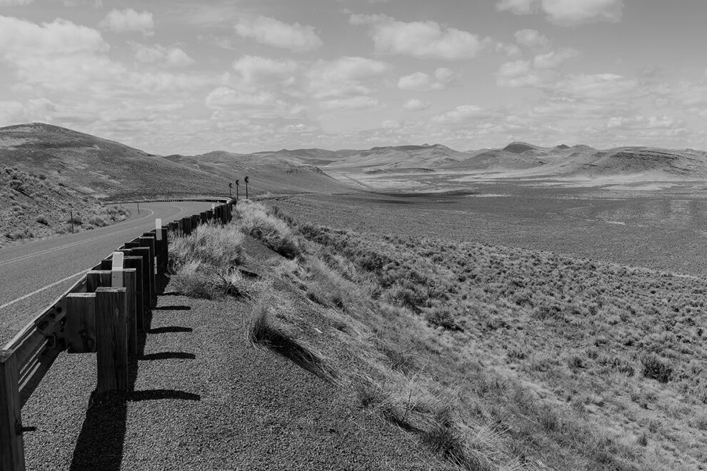 Black and white photo of roadside and rural landscape in Malheur County, Oregon.