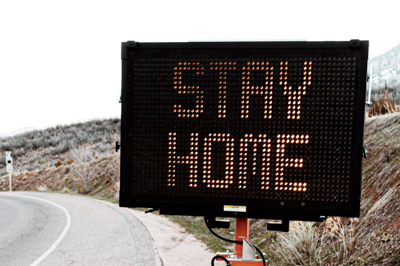 Traffic sign on roadside that reads 'Stay Home'.