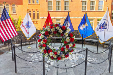 A wreath of flowers, the American flag and military flags at the WSU Veterans Memorial.