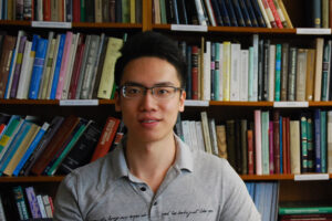 Yan Su portrait in front of book shelves