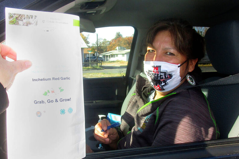 A woman receives Inchelium Red garlic at a drive-through event.
