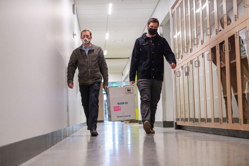 Two people carrying a carton of COVID-19 vaccine down a hallway