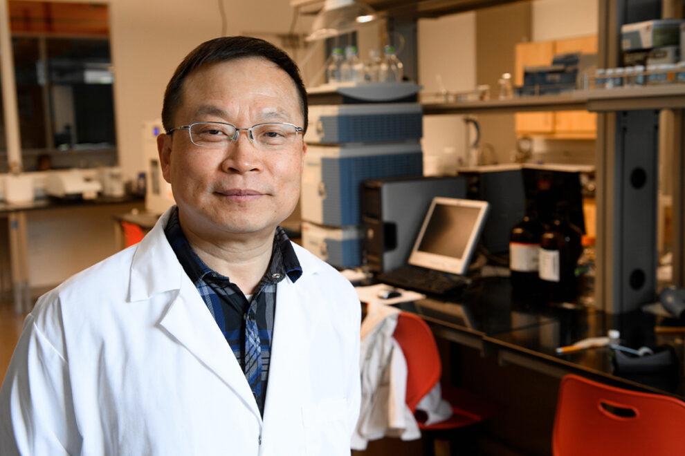 Closeup of Jinwen Zhang in laboratory.