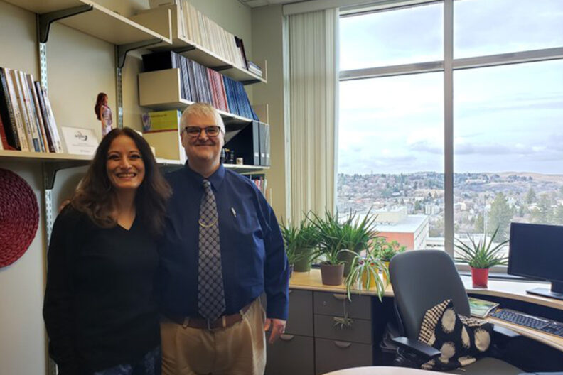 Paul Bolls and Porismita Borah pose for a picture in an office.
