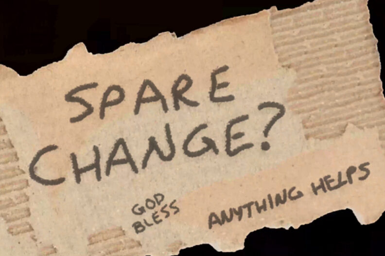 A small sign with spare change? written on it.
