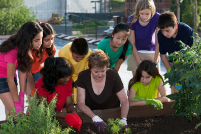 A teacher shows young students how to grow plants