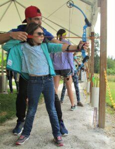 Camp Korey participant practices archery.