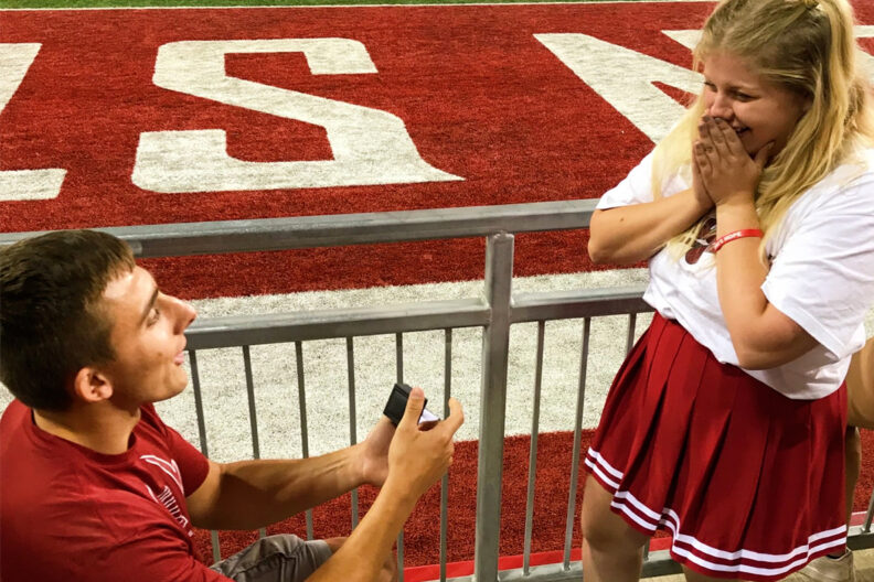 Man proposing to woman at WSU Cougars football game.