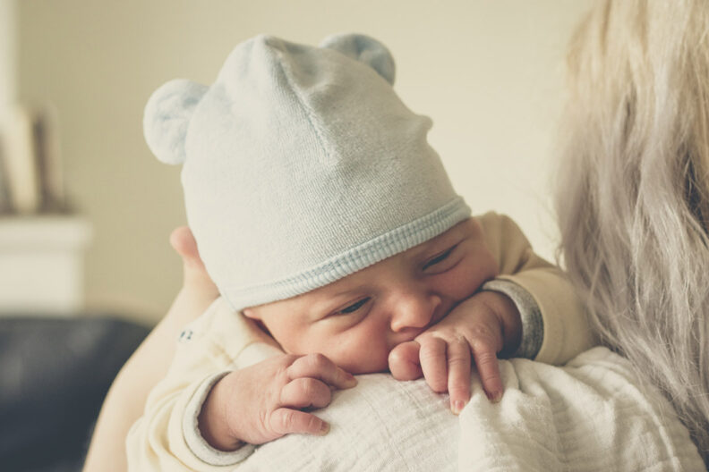 Newborn baby in hat on the shoulder of her mother