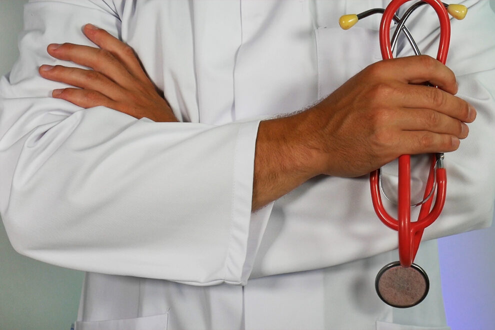 Closeup of a doctor's arms crossed while holding a stethoscope.
