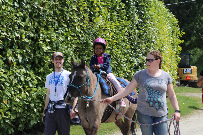 A young girl rides a horse while two camp counselors help