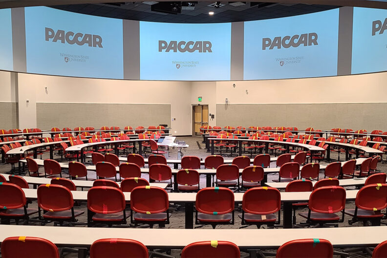 Rows of empty tables and chairs inside the PACCAR Lecture Hall.