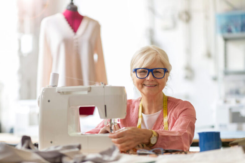Woman sitting at a sewing machine.