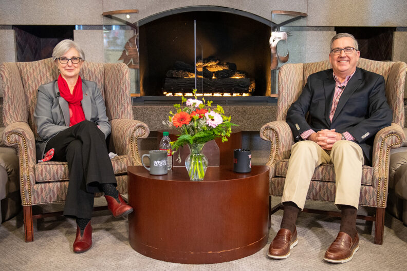 WSU President Kirk Schulz and WSU Provost Elizabeth Chilton sitting in chairs next to a fireplace.