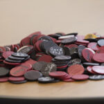 A pile of tokens with positive phrases written on them.
