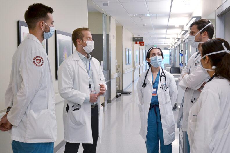 Doctors confer in a hallway