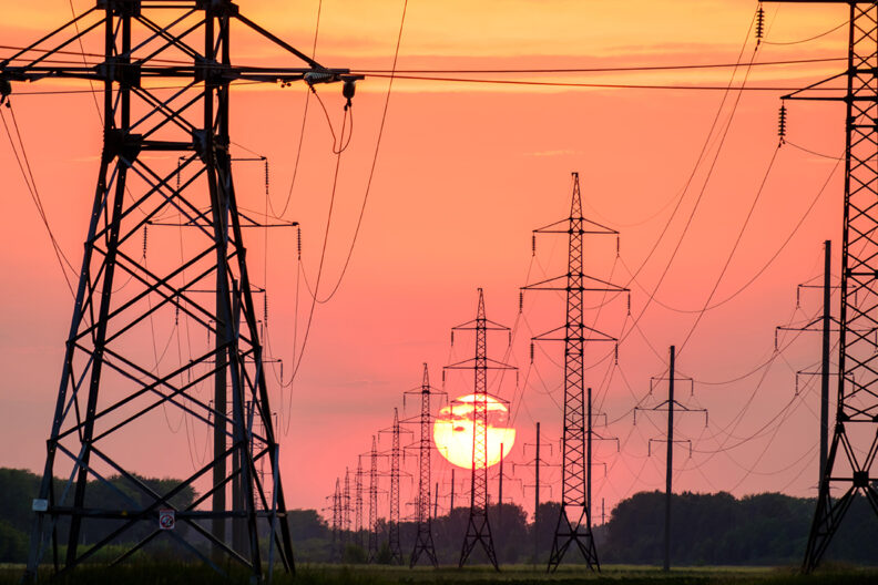 Rows of electric power lines fill the sky as the sun sets.