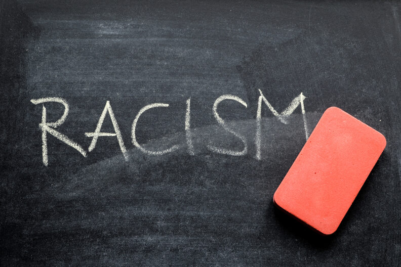 Chalkboard with 'racism' written on it and partially erased.