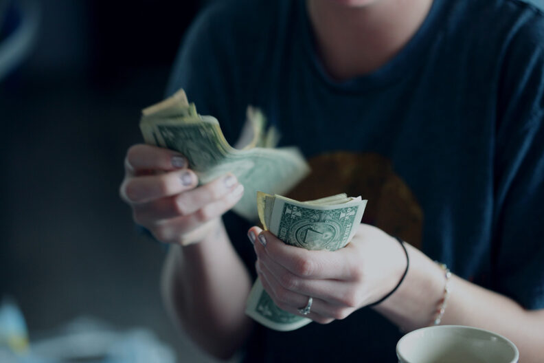 Closeup of a woman's hands while counting U.S. dollars.