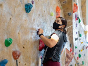 Student wearing a mask and using the rock wall.