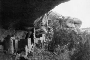 Historical black and white image of a Pueblo cliff dwelling.