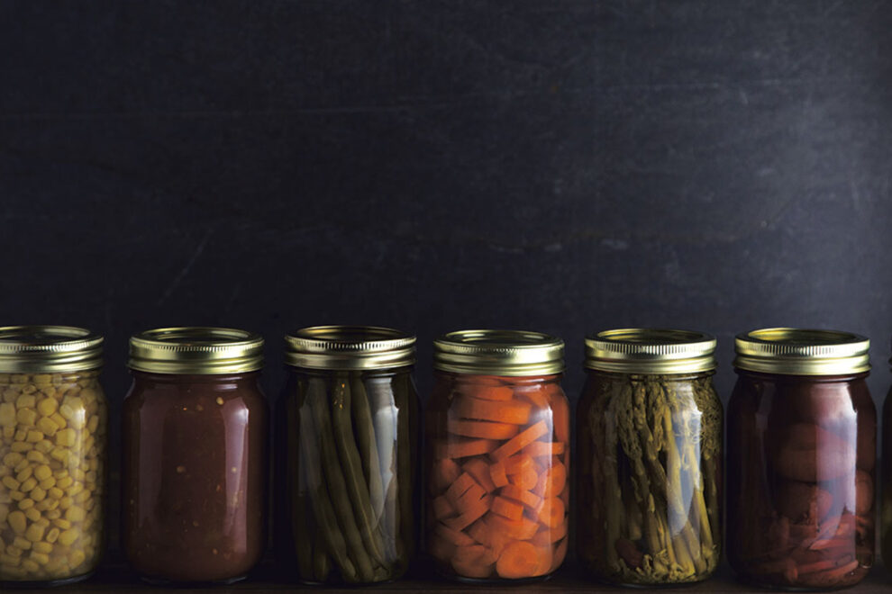 A row of various foods in canning jars.